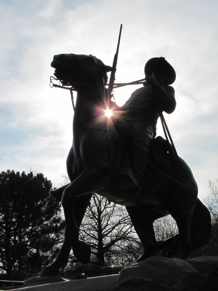 Backlit photo of the Buffalo Soldier statue.