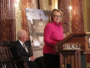 Secretary of State Hillary Rodham Clinton speaking at launch of new US Diplomacy Center. Former secretary James Baker III is behind her.