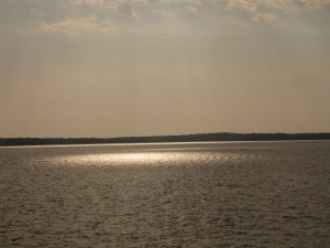 The golden glow of the rising sun on the dark blue water of Chesapeake Bay.