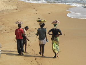 Vendors walking along the beach south of Douala.