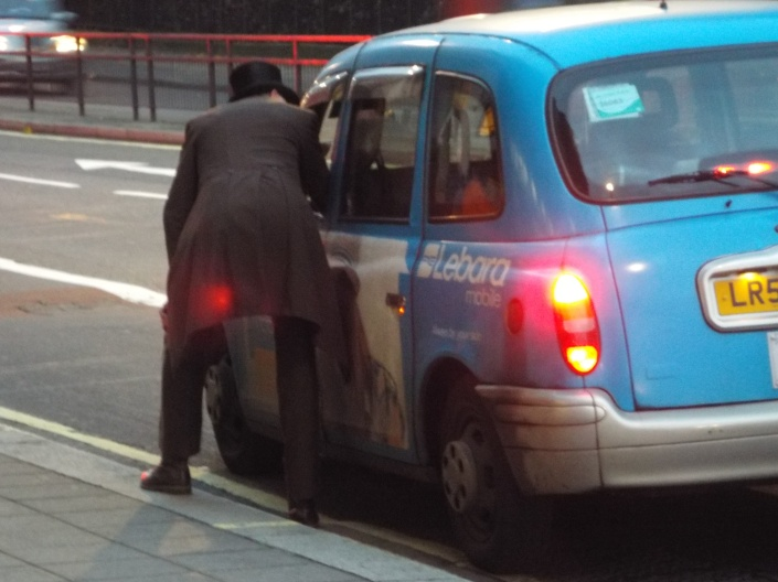 A hotel doorman, complete with top hat, at a hotel in Central London, chats with a cabbie.